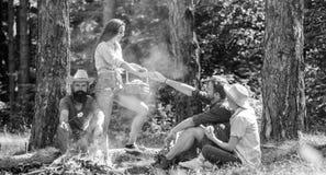 Φίλοι που χαλαρώνουν κοντά στη φωτιά Οι φίλοι απολαμβάνουν το πικ-νίκ τρώνε το δασικό υπόβαθρο φύσης τροφίμων Σχέδιο για το τέλει στοκ φωτογραφία με δικαίωμα ελεύθερης χρήσης