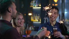 Φίλοι που χαλαρώνουν στο φραγμό με τα ποτά και τα σπινθηρίσματα απόθεμα βίντεο