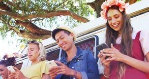 Φίλοι που χρησιμοποιούν το κινητό τηλέφωνο κοντά στο φορτηγό τροχόσπιτων στο πάρκο 4k φιλμ μικρού μήκους