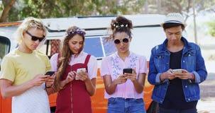 Φίλοι που χρησιμοποιούν το κινητό τηλέφωνο κοντά στο φορτηγό τροχόσπιτων στο πάρκο 4k απόθεμα βίντεο