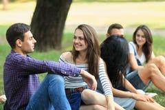 Φίλοι στο πάρκο, νέα γυναίκα και επικοινωνία ανδρών Στοκ φωτογραφία με δικαίωμα ελεύθερης χρήσης