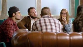 Φίλοι συνεδρίασης στον καφέ Νέοι που μιλούν και που τρώνε την πίτσα σε έναν καφέ φιλμ μικρού μήκους