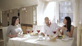 Φίλοι συνεδρίασης στο εστιατόριο Ευτυχείς φίλοι που τρώνε και που πίνουν στο εστιατόριο Τέσσερις φίλοι στο εστιατόριο, τρώνε απόθεμα βίντεο