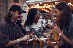 Φίλοι Hipster που κουβεντιάζουν ενώ έχοντας το μεσημεριανό γεύμα στον υπαίθριο καφέ στοκ φωτογραφία με δικαίωμα ελεύθερης χρήσης