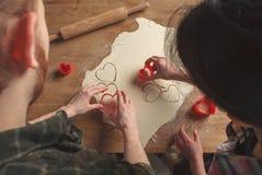 Φίλος και φίλη, που κατασκευάζουν τα μπισκότα για την ημέρα βαλεντίνων ` s tog Στοκ Φωτογραφίες