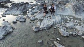 Φίλος και φίλη στον άγριο απότομο βράχο θάλασσας απόθεμα βίντεο