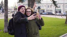 Φίλος που παίρνει τη φωτογραφία της φίλης στο κέντρο της πόλης φιλμ μικρού μήκους