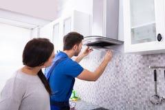 Φίλτρο εξολκέων κουζινών καθορισμού επισκευαστών πέρα από το μετρητή κουζινών στοκ φωτογραφίες με δικαίωμα ελεύθερης χρήσης