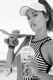 Φίλαθλη γυναίκα με skateboard το πόσιμο νερό ενάντια στον ουρανό Στοκ Εικόνα