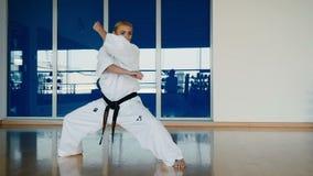Φίλαθλη γυναίκα που ασκεί τις karate μετακινήσεις στη γυμναστική απόθεμα βίντεο