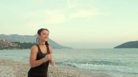 Φίλαθλη γυναίκα που τρέχει στην παραλία ακροθαλασσιών το πρωί απόθεμα βίντεο