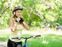 Φίλαθλη γυναίκα στο ποδήλατο βουνών που βάζει το biking κράνος Στοκ Εικόνα