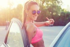 Φίλαθλη κατάλληλη νέα γυναίκα αθλητών στον αθλητικό στηθόδεσμο που φορά τη στάση γυαλιών ηλίου που κλίνει στο αυτοκίνητο με την α Στοκ φωτογραφία με δικαίωμα ελεύθερης χρήσης