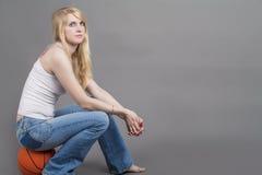 Φίλαθλη καυκάσια ξανθή θηλυκή συνεδρίαση στη σφαίρα καλαθοσφαίρισης στο στήριγμα Στοκ φωτογραφία με δικαίωμα ελεύθερης χρήσης