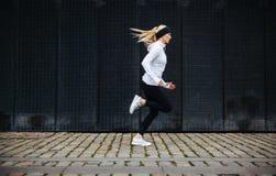 Φίλαθλη νέα γυναίκα που τρέχει στο πεζοδρόμιο το πρωί Στοκ Εικόνες