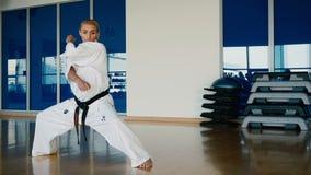 Φίλαθλη ξανθή γυναίκα που παρουσιάζει μερικά karate τεχνάσματα στη γυμναστική φιλμ μικρού μήκους