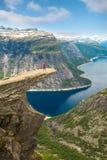 Φίλαθλη τοποθέτηση γυναικών σε Trolltunga Νορβηγία Στοκ εικόνα με δικαίωμα ελεύθερης χρήσης