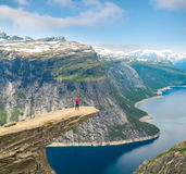 Φίλαθλη τοποθέτηση γυναικών σε Trolltunga Νορβηγία Στοκ Φωτογραφία