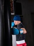 Φίλαθλος αρσενικός μπόξερ στα εγκιβωτίζοντας γάντια που εκπαιδεύει με τον εγκιβωτισμό punching Στοκ Εικόνα