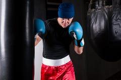 Φίλαθλος μπόξερ στα εγκιβωτίζοντας γάντια που εκπαιδεύει με τον εγκιβωτισμό punching της τσάντας Στοκ φωτογραφία με δικαίωμα ελεύθερης χρήσης