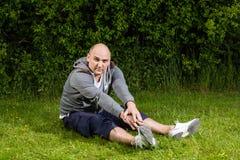 Φίλαθλο άτομο που κάνει την τεντώνοντας άσκηση στο πράσινο λιβάδι Στοκ Φωτογραφίες