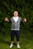 Φίλαθλο άτομο που κρατά δύο κόκκινους αλτήρες στον αέρα Στοκ φωτογραφία με δικαίωμα ελεύθερης χρήσης