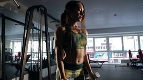 Φίλαθλο κορίτσι που παρουσιάζει την καλά - εκπαιδευμένο σώμα και που ανυψώνει τους αλτήρες απόθεμα βίντεο