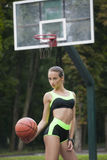 Φίλαθλο κορίτσι που στέκεται με μια σφαίρα καλαθοσφαίρισης Στοκ Εικόνες