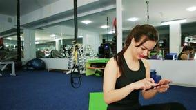 Φίλαθλο κορίτσι που χαμογελά στη νέα λήψη γυναικών καμερών selfie κάνοντας τις ασκήσεις ικανότητας σε μια σύγχρονη γυμναστική, πο απόθεμα βίντεο