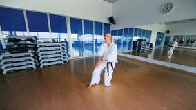 Φίλαθλο κορίτσι στο κιμονό που ασκεί karate στη γυμναστική απόθεμα βίντεο