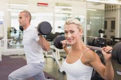 Φίλαθλο νέο ζεύγος που ανυψώνει barbells στη γυμναστική στοκ εικόνα