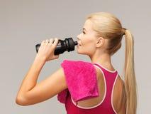 Φίλαθλο πόσιμο νερό γυναικών από το μπουκάλι αθλητικών τύπων Στοκ Φωτογραφία
