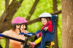 Φίλαθλο mom και το παιδί της, που κάθονται στο κάθισμα ποδηλάτων Στοκ Φωτογραφία