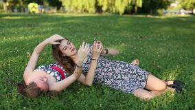 Φίλες κοριτσιών εφήβων που βρίσκονται στο χορτοτάπητα που παίρνει τις εικόνες του σε ένα κινητό τηλέφωνο, selfie απόθεμα βίντεο