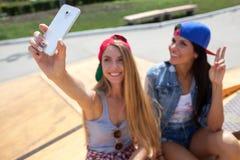 Φίλες που παίρνουν μια φωτογραφία selfie στο πάρκο σαλαχιών στοκ εικόνα