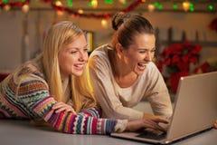 Φίλες που χρησιμοποιούν το lap-top στην κουζίνα Χριστουγέννων Στοκ φωτογραφία με δικαίωμα ελεύθερης χρήσης