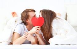 Φίλημα ζευγών εραστών με μια κόκκινη καρδιά στο κρεβάτι Στοκ Εικόνες