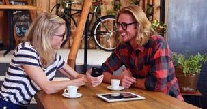Φίλη που παρουσιάζει smartphone στο φίλο φιλμ μικρού μήκους