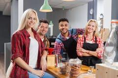 Φίλοι ανθρώπων που πίνουν την ομιλία καφετεριών που γελά με τη συνεδρίαση barista στο μετρητή φραγμών Στοκ Εικόνες