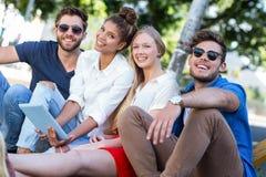 Φίλοι ισχίων που κρατούν την ταμπλέτα και που κάθονται στο πεζοδρόμιο Στοκ εικόνα με δικαίωμα ελεύθερης χρήσης