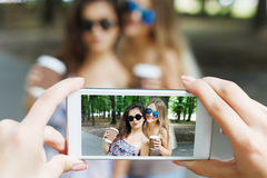 Φίλοι κοριτσιών που παίρνουν τις φωτογραφίες με το smartphone υπαίθρια Στοκ φωτογραφίες με δικαίωμα ελεύθερης χρήσης