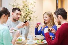Φίλοι με τα smartphones που παίρνουν την εικόνα των τροφίμων Στοκ φωτογραφία με δικαίωμα ελεύθερης χρήσης