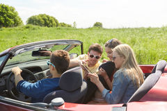 Φίλοι με την οδήγηση PC ταμπλετών στο αυτοκίνητο καμπριολέ Στοκ Φωτογραφίες