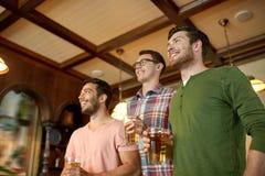 Φίλοι με τον αθλητισμό προσοχής μπύρας στο φραγμό ή το μπαρ Στοκ φωτογραφία με δικαίωμα ελεύθερης χρήσης