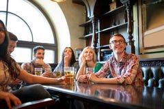 Φίλοι με το ποδόσφαιρο προσοχής μπύρας στο φραγμό ή το μπαρ Στοκ Φωτογραφίες