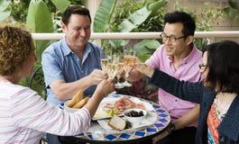 Φίλοι που έχουν ένα ευχάριστο μεσημεριανό γεύμα της Κυριακής Στοκ φωτογραφία με δικαίωμα ελεύθερης χρήσης