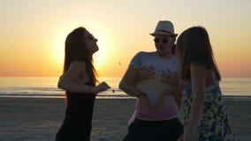 Φίλοι που έχουν ένα κόμμα διασκέδασης στην ακτή της θάλασσας στην ανατολή απόθεμα βίντεο