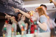 Φίλοι που έχουν ένα ποτό μαζί και που δείχνουν κάτι Στοκ φωτογραφία με δικαίωμα ελεύθερης χρήσης