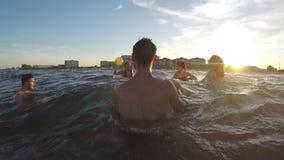 Φίλοι που έχουν τη διασκέδαση και που παίζουν την πετοσφαίριση στη θάλασσα στο καλοκαίρι απόθεμα βίντεο