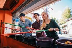 Φίλοι που έχουν τη διασκέδαση με το παιχνίδι αλιείας στο λούνα παρκ Στοκ Εικόνες